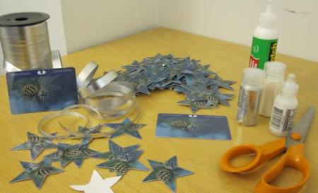 Askartelua varten varasimme hopeanauhaa, vahvaa liimaa, hilettä, tarroja ja glitteriliimaa. Leikkasimme paperista tehdyn malliin mukaan kirjastokorteista laatikollisen tähtiä.