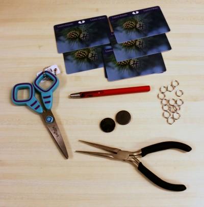 Päätarvikkeet: vanhoja kirjastokortteja, sakset, pihdit, renkaita, magneetteja ja nahkapaska. Lisäksi osassa käytettiin kirppiksen lasten muovieläimiä ja jäämäkankaita.