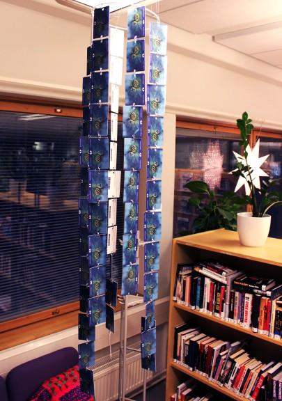 Mobile vanhoista kirjastokorteista. Kortit reitetty molemmista päistä, väliin laitettu rengas.
