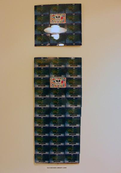 Kirjastokorttitaulu: Kirjastokortteja liimattu vaneeriin kiinni, päällä vaihtokehys. Kauempaa katsottuna näyttää kuin seinällä olisi rahaa lasin alla.