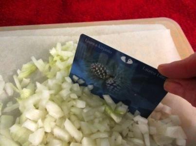 Kirjastokorttia voi käyttää pilkkomisen apuna. Ensin sipulit isoiksi lohkoiksi ja hienonnus kirjastokortilla.